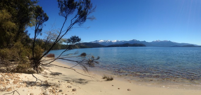 Looking out to the Fiordland mountains from the sandy shores on the Lake Manapouri circle Track