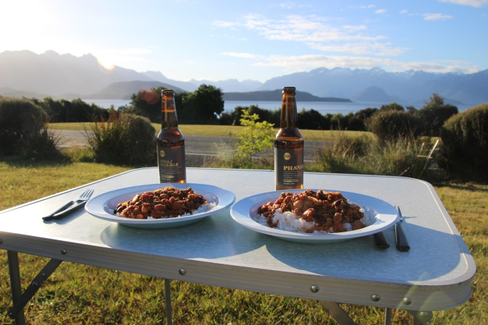 Dinner and beer on a table overlooking Lake Manapouri as the sun sets